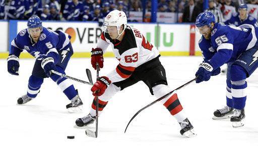 New Jersey Devils left wing Jesper Bratt (63) gets between Tampa Bay Lightning defensemen Dan Girardi (5) and Braydon Coburn (55) during the third period of Game 5 of an NHL first-round hockey playoff series Saturday, April 21, 2018, in Tampa, Fla.