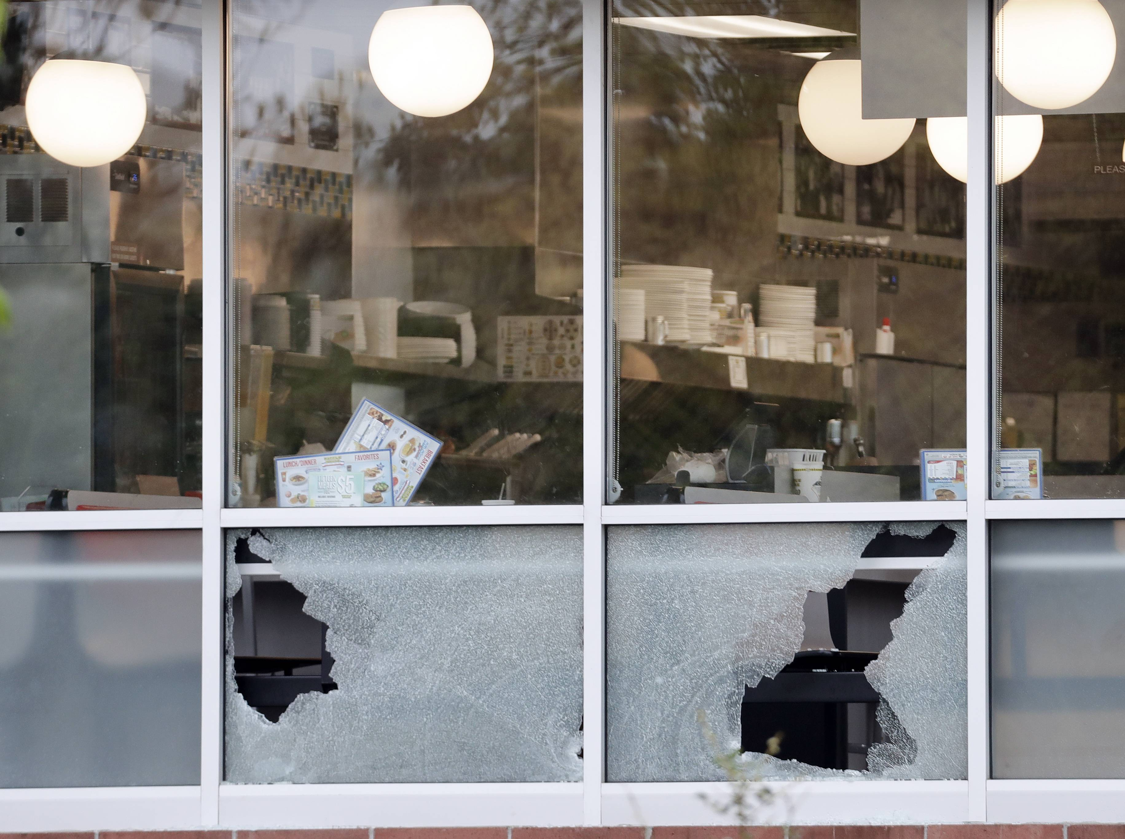 Menus sit on tables next to windows shot out at a Waffle House restaurant Sunday in Nashville, Tennessee, where four people died.