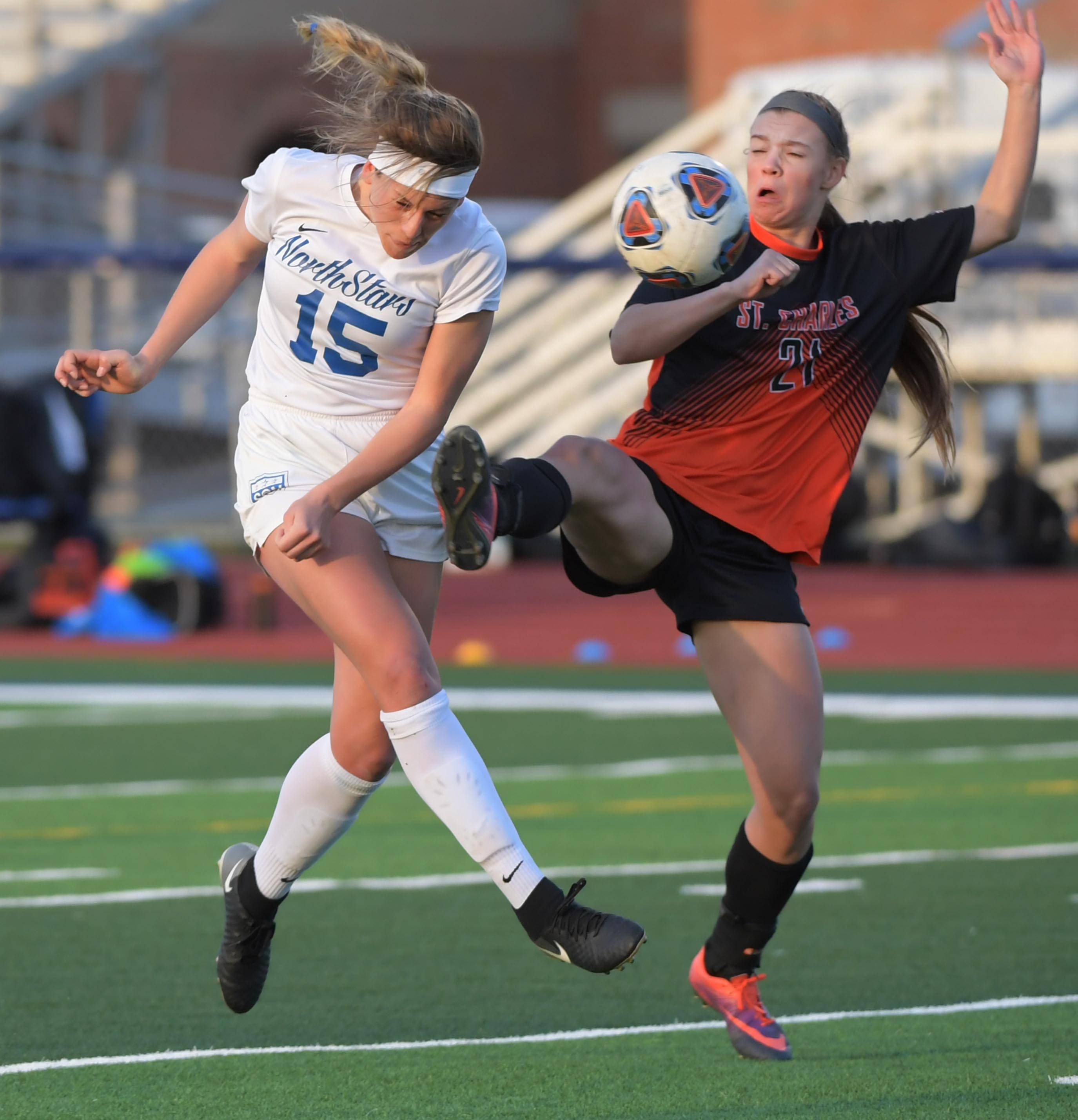 St. Charles North's Gia Wahlberg heads the ball for a goal against St. Charles East's Megan Stout in the first half of a girls soccer game at North High School Tuesday.