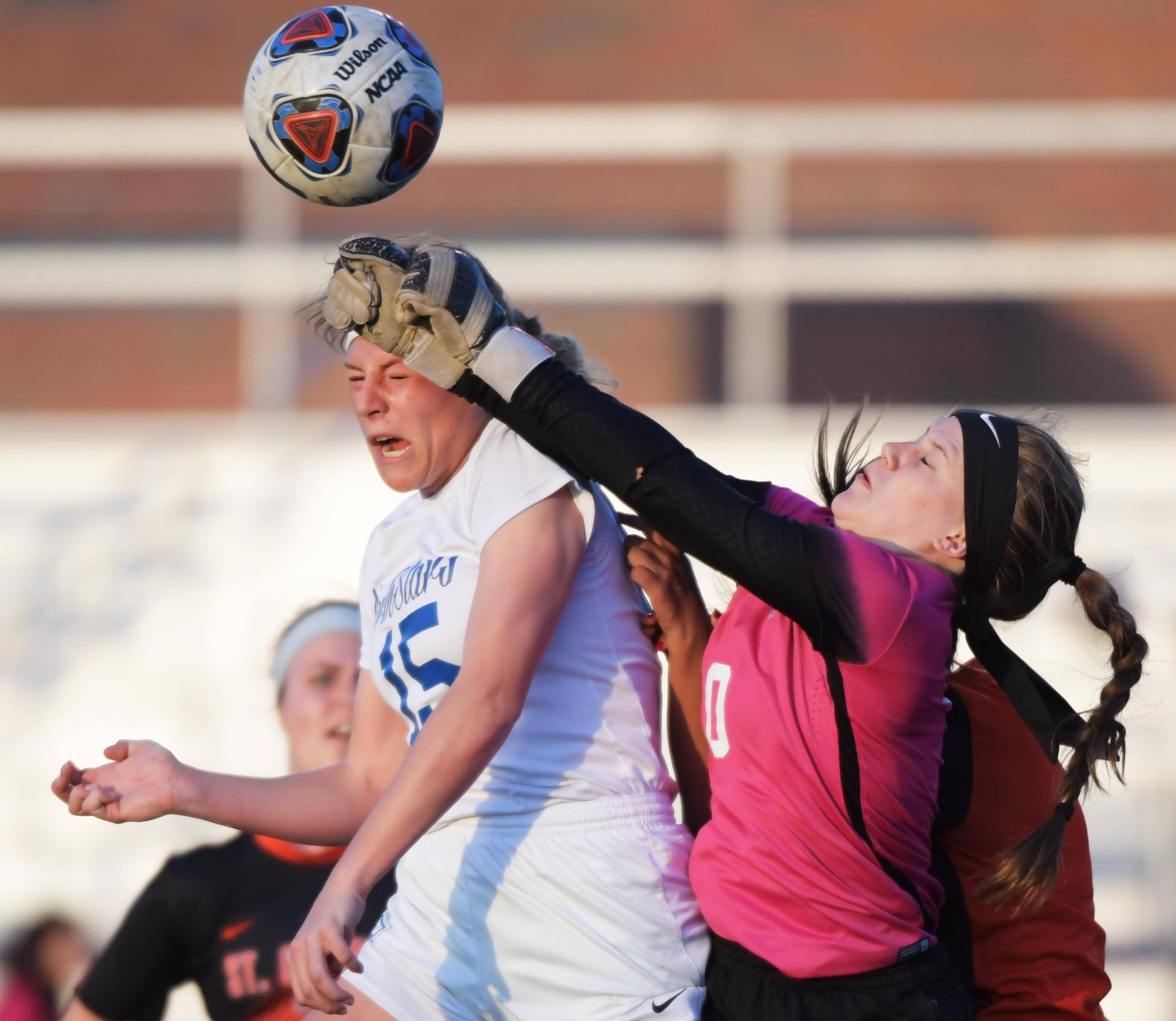 St. Charles East goalkeeper Grace Griffin punches the ball away from St. Charles North's Gia Wahlberg in a girls soccer game at North High School Tuesday.