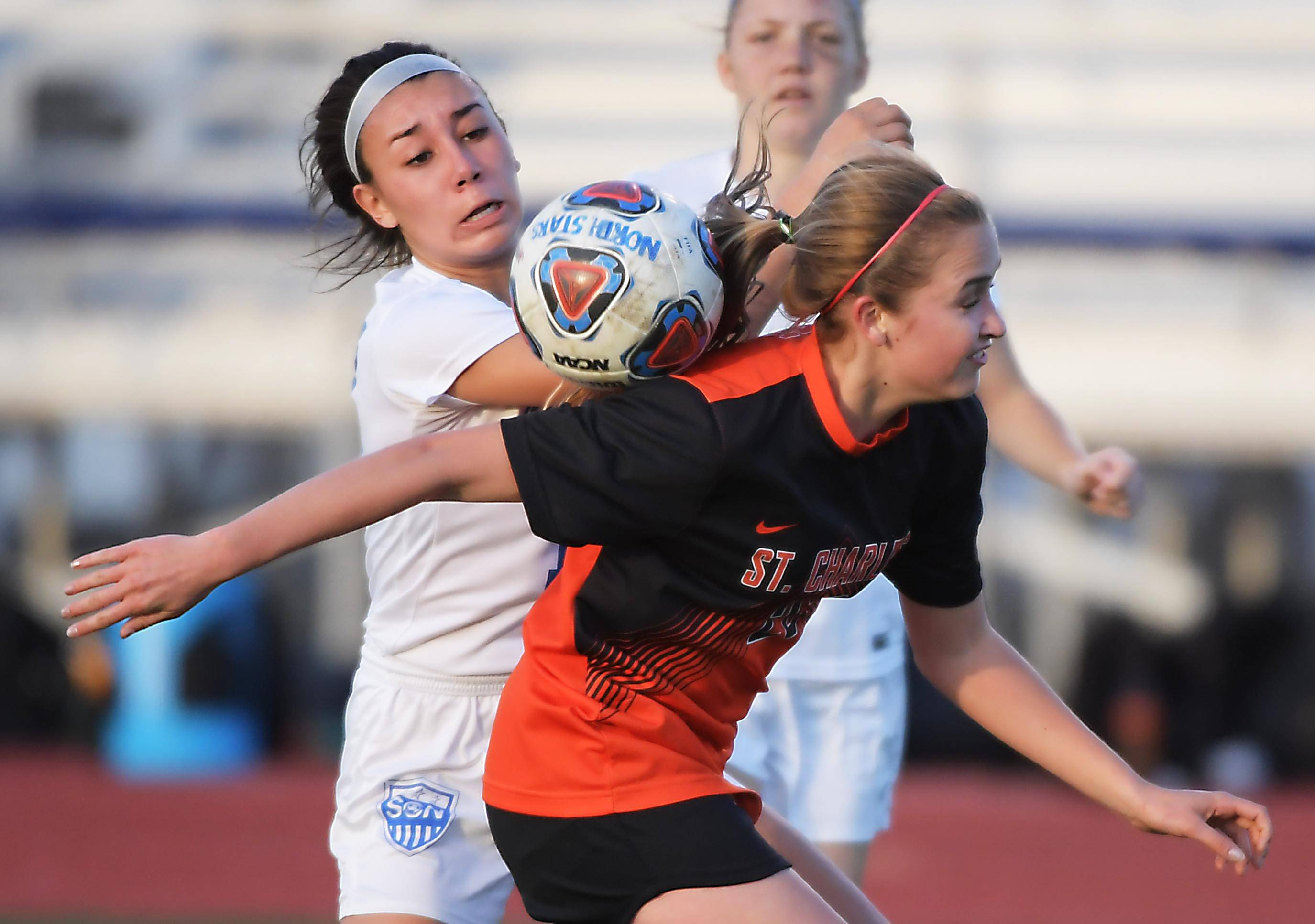 St. Charles North's Claudia Najera keeps her eye on the ball as it bounces on the shoulder of St. Charles East's Lindsey Rzeszutko in a girls soccer game at North High School Tuesday.