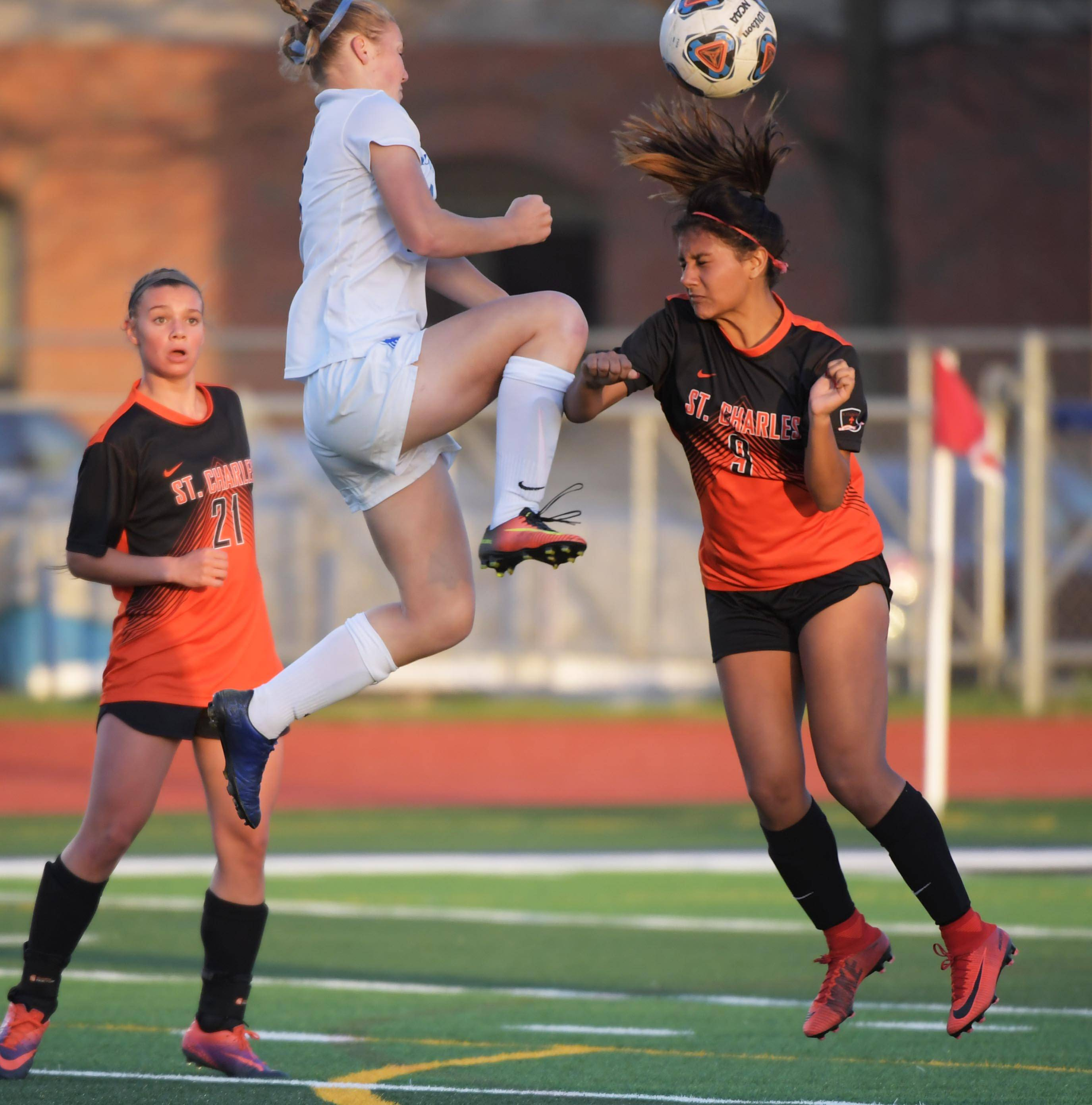 St. Charles North's Sarah Andrey and St. Charles East's Alondra Carranza collide in a girls soccer game at North High School Tuesday.