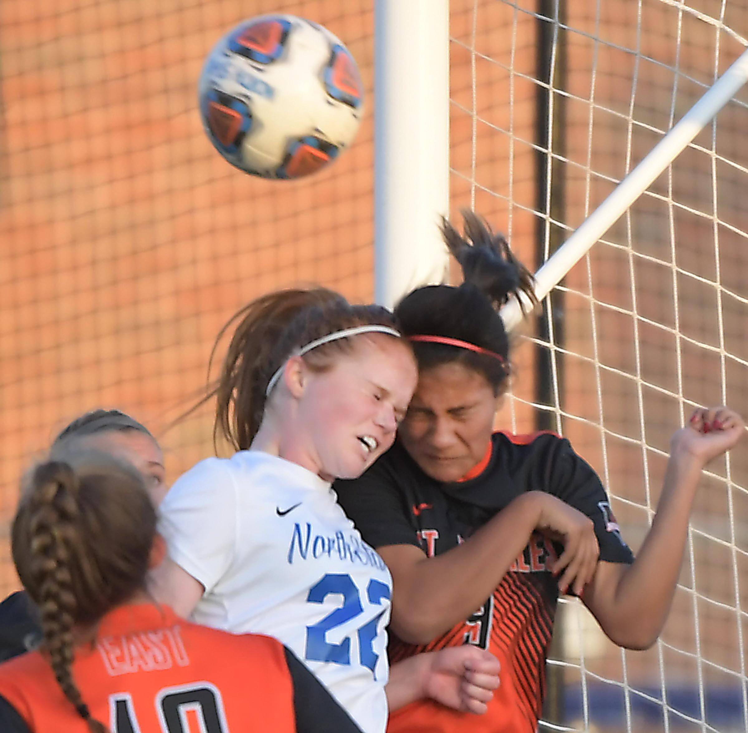 St. Charles North's Cassidy Joyce and St. Charles East's Alondra Carranza collide as they head the ball in a girls soccer game at North High School Tuesday.