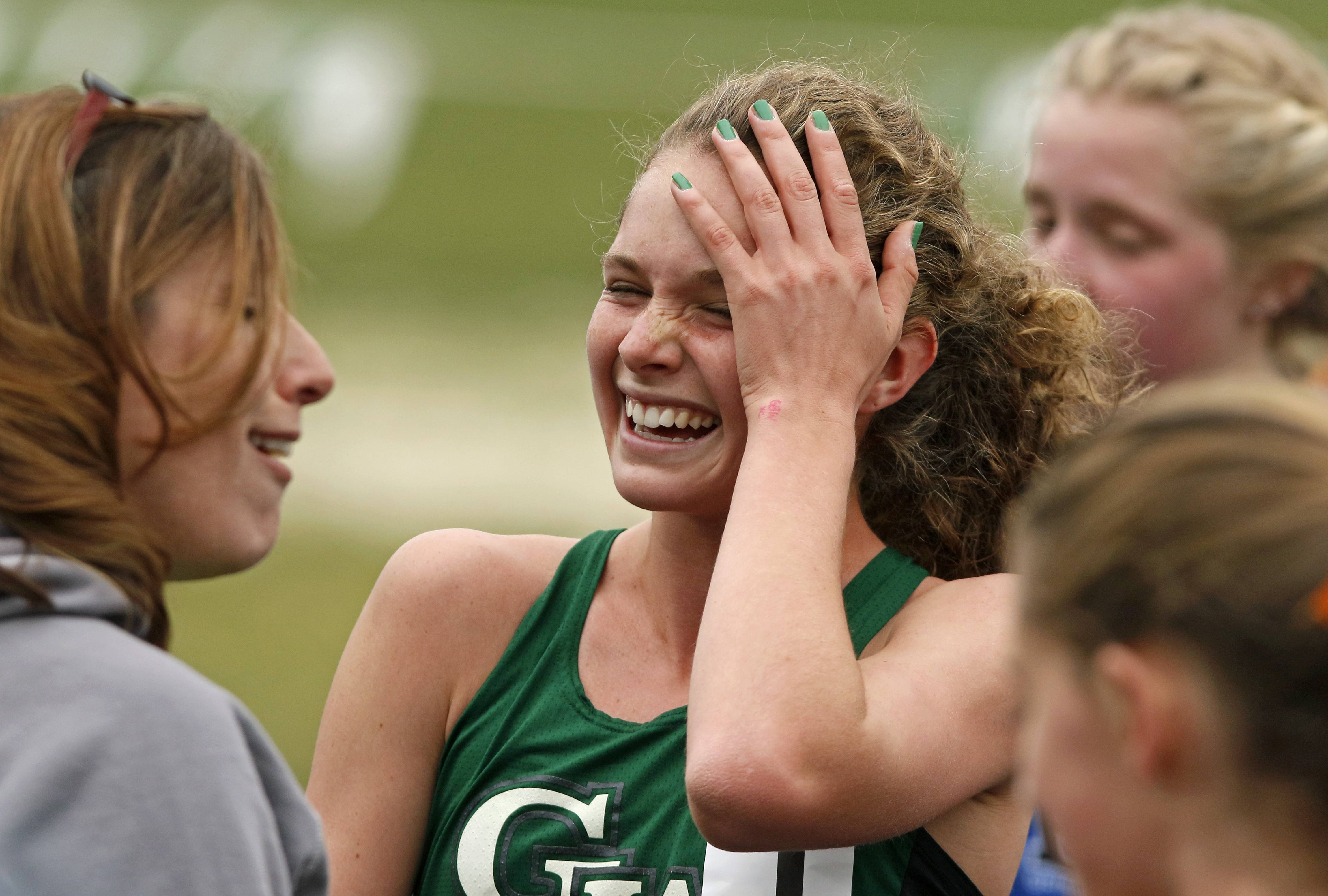 Glenbard West's Katelynne Hart reacts to her 3200-meter run time during the Glenbard West Girls Track Invite. The IHSA considers only all-time records set at the state meet, but Hart ran what is believed to be the second-fastest time in U.S. history Saturday morning with her time of 9 minutes, 52.02 seconds. California native Kim Mortensen set the American high school record in 1996 with her 9:48.59.
