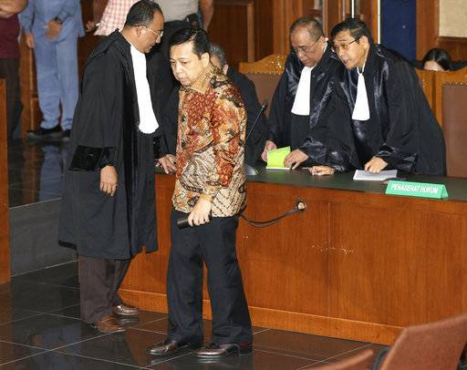 Former Indonesia's Parliament Speaker Setya Novanto walks after talking with his lawyer during his sentencing hearing at the Corruption Cases Court in Jakarta, Indonesia, Tuesday, April 24, 2018. The court sentenced the senior politician to 15 years in prison for his role in the theft of $170 million of public money by officials, a victory for anti-corruption police fighting the country's rampant graft.