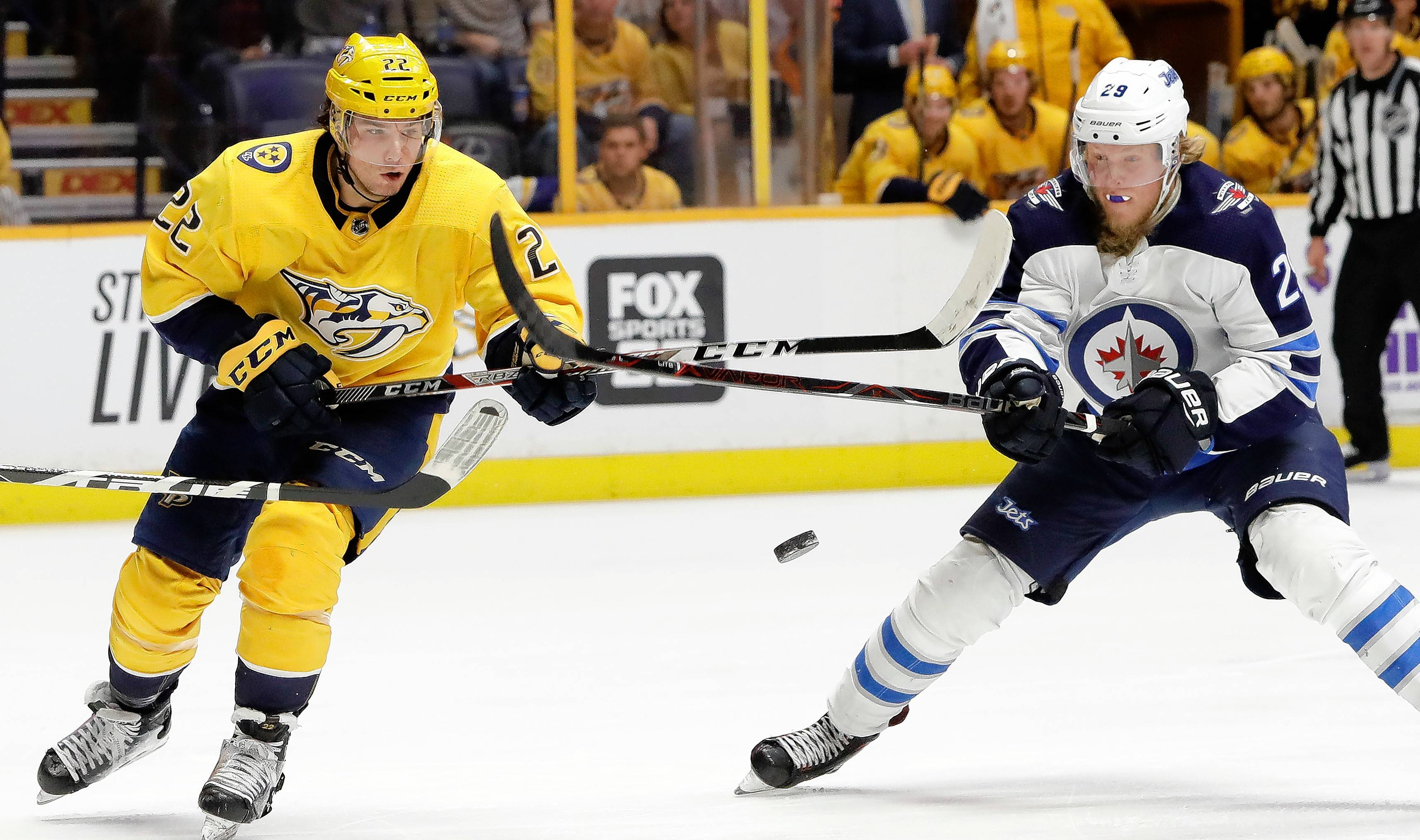 Nashville Predators left wing Kevin Fiala (22) and Winnipeg Jets right wing Patrik Laine (29) battle for the puck in a game last month in Nashville, Tenn.