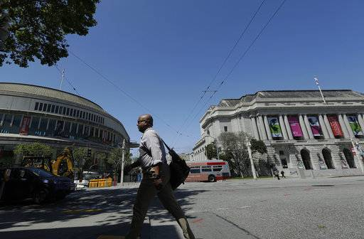 A man walks along Van Ness Avenue across the street from Louise M. Davies Symphony Hall, left, and War Memorial Opera House in San Francisco, Wednesday, April 25, 2018. The San Francisco Conservatory of Music plans to start construction this summer of a 12-floor building containing two concert halls in an area that already includes City Hall, the San Francisco Opera and the San Francisco Symphony's Davies Hall.
