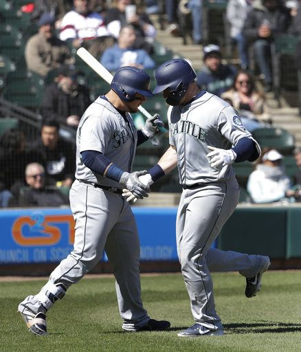 Seattle Mariners' Daniel Vogelbach, left, greets Mike Zunino at home after Zunino's home run off Chicago White Sox starting pitcher James Shields during the sixth inning of a baseball game Wednesday, April 25, 2018, in Chicago.
