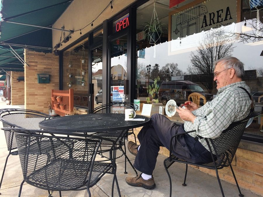 Martin Lindwall enjoys a cafe mocha Thursday outside the Area General Store in Mundelein. Village officials are developing rules for restaurants and other businesses that want to create dining or seating areas on public sidewalks.