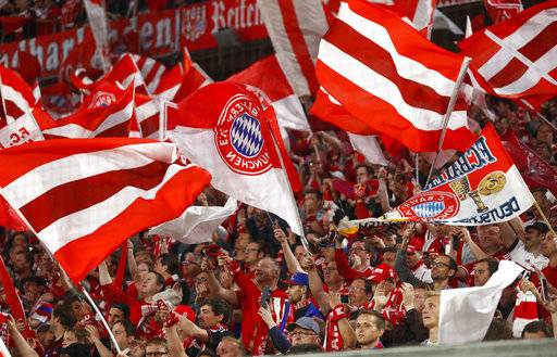 Bayern fans wave flags prior to the semifinal first leg soccer match between FC Bayern Munich and Real Madrid at the Allianz Arena stadium in Munich, Germany, Wednesday, April 25, 2018.