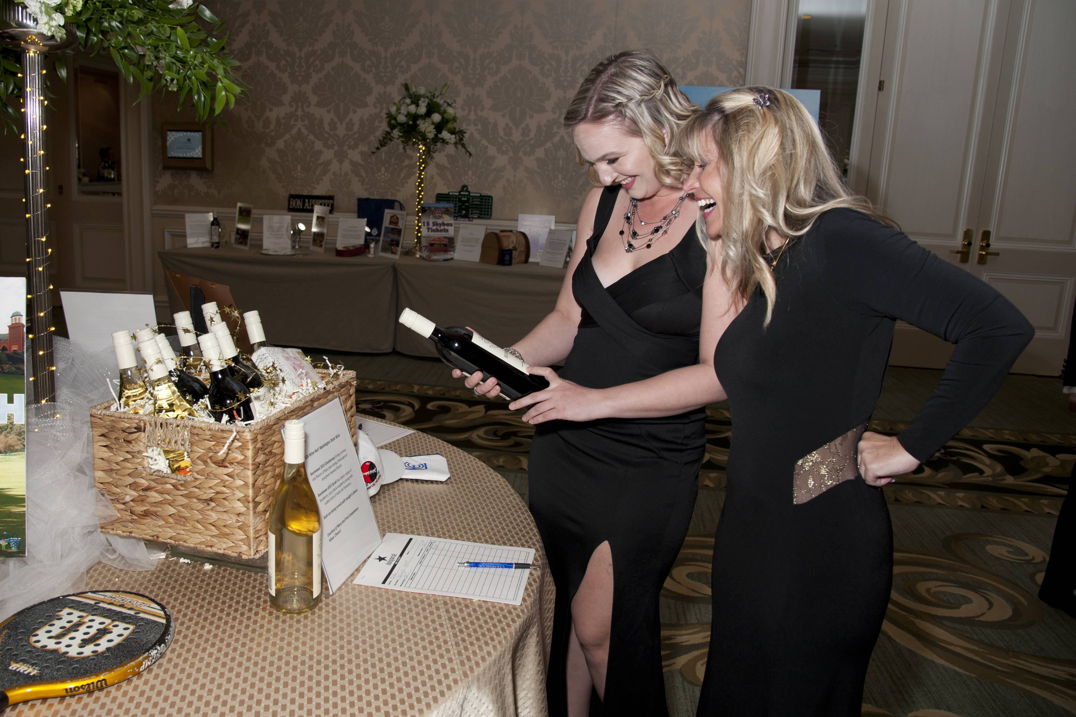 COURTESY OF ROBERT CARLBrooke Wils and Laura Warren look at silent auction items during the Clearbrook Event at the Four Seasons Hotel Chicago on Friday, April 27, 2018.