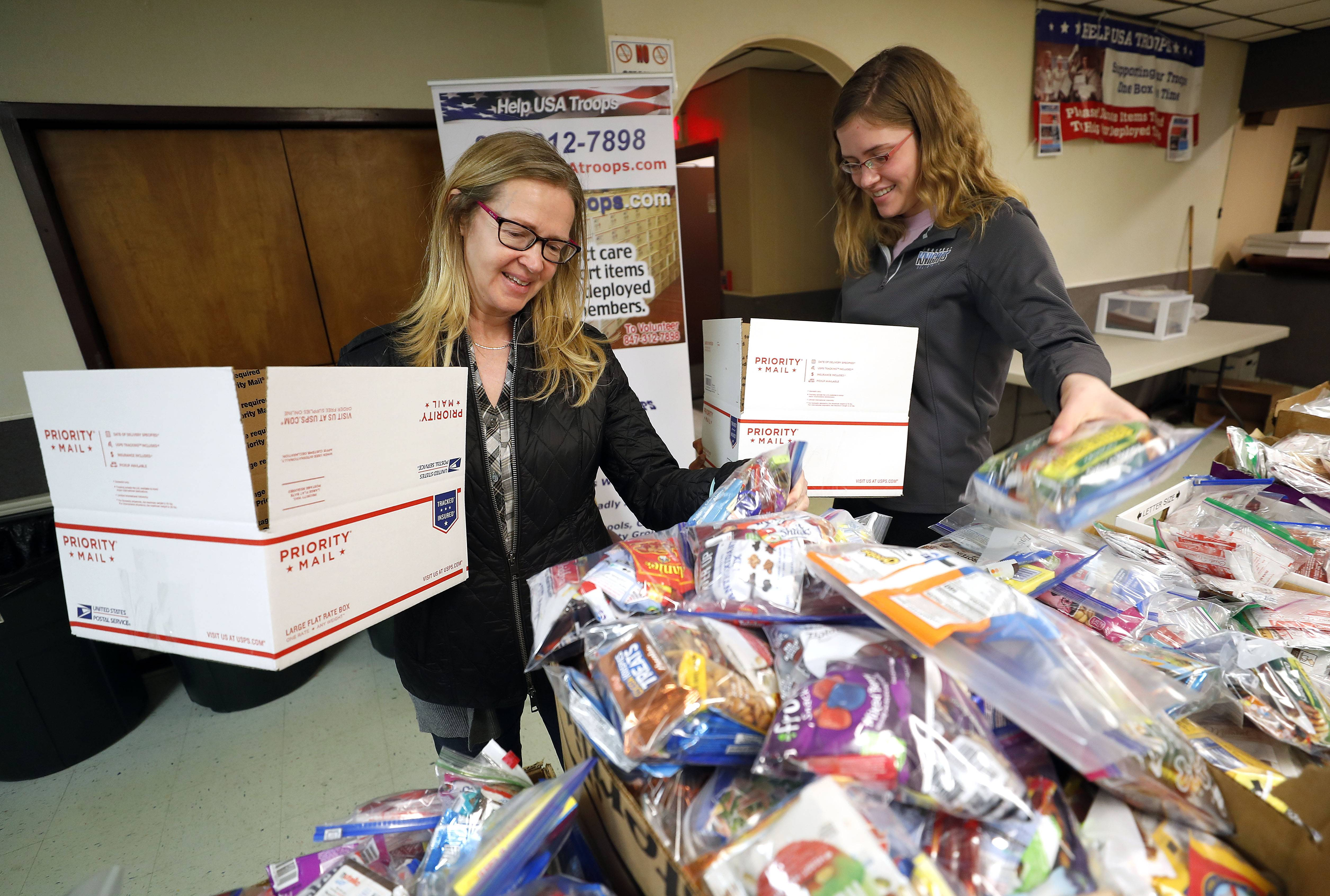 Kathi Inorio, left, and her daughter Grace, both of Mount Prospect, fill boxes as Help USA Troops held a shipping party Sunday at AMVETS Post 66 in Wheeling.