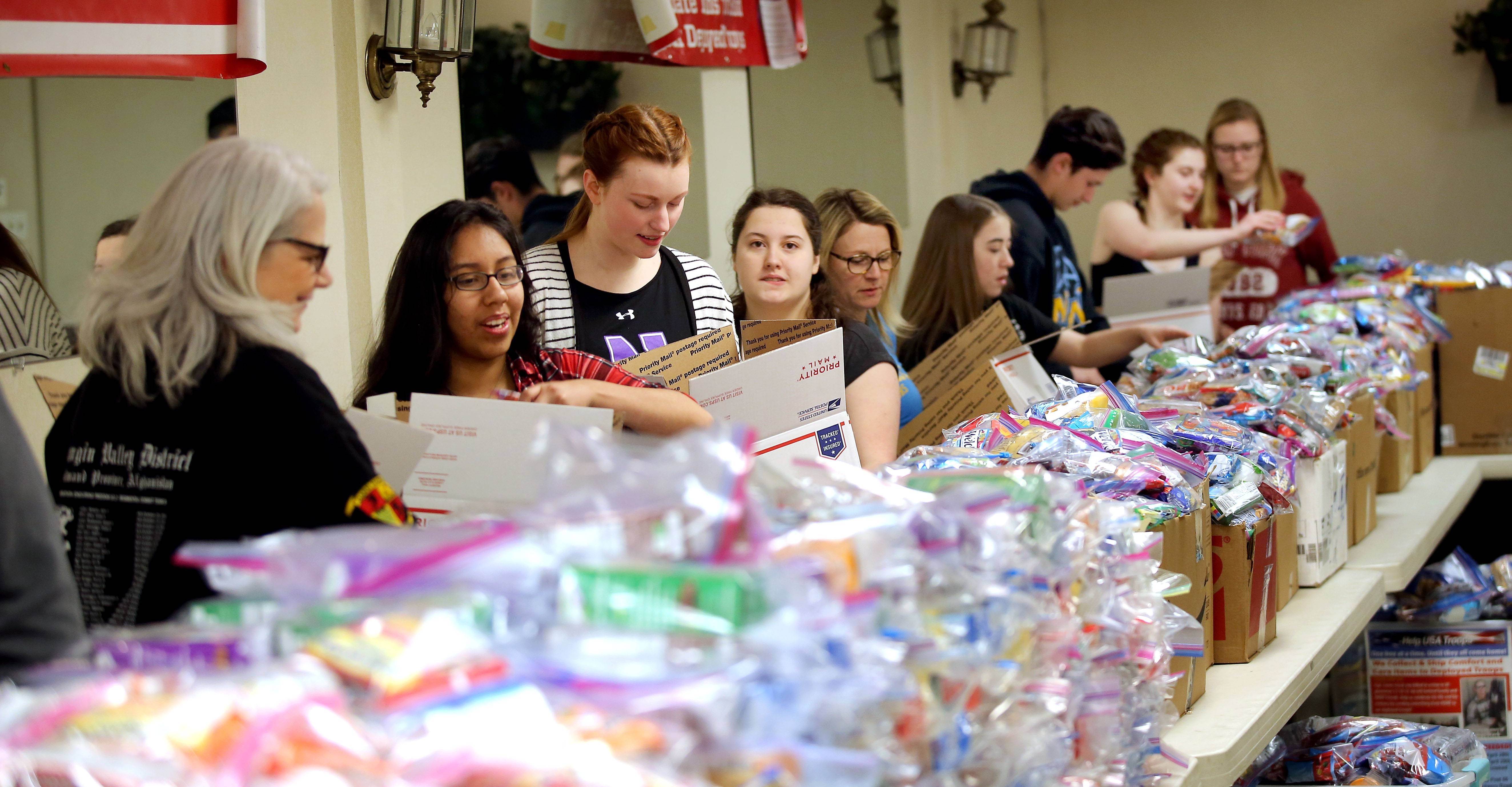 Volunteers line up to fill boxes Sunday as Help USA Troops held a shipping party at AMVETS Post 66 in Wheeling. The goal of the day was to ship 700 or more boxes containing comfort and care items to deployed troops.