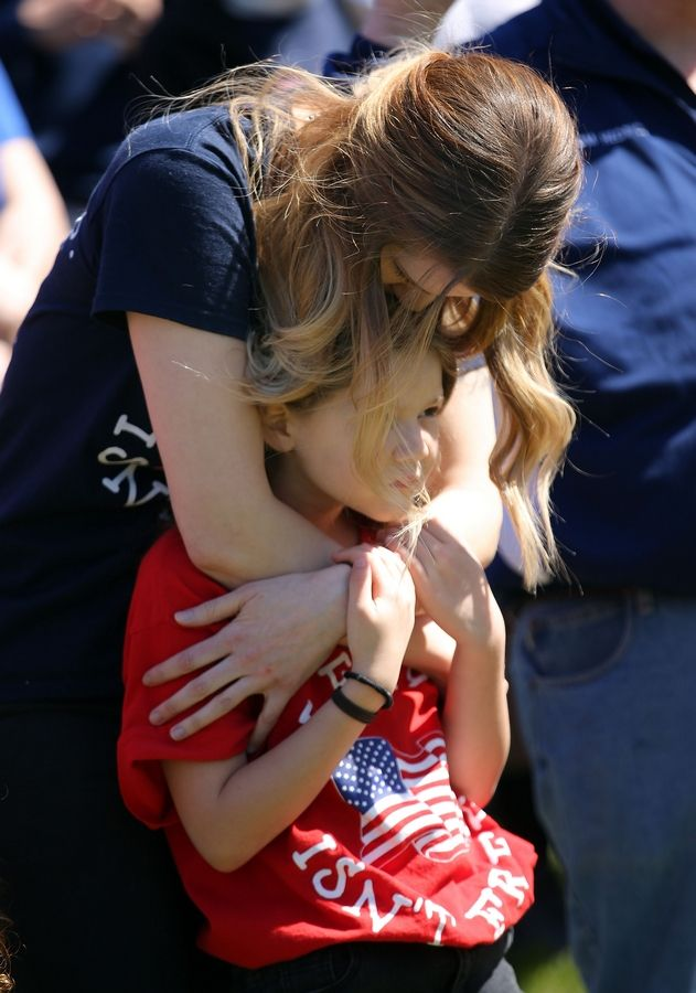 Katie Stack hugs her 8-year-old daughter, Mikayla, during a performance of the national anthem Sunday as Help USA Troops held an event at AMVETS Post 66 in Wheeling to ship 700 or more boxes containing comfort and care items to deployed troops. Help USA Troops was founded in memory of Stack's husband, James, a U.S. Marine from Arlington Heights killed in 2010 while serving in Afghanistan.