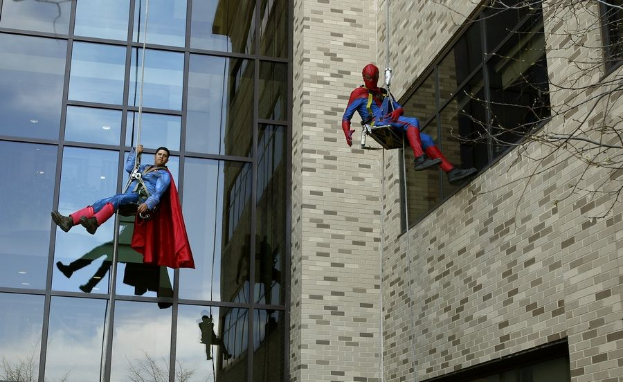 For the past five years, window washers from TJ Maintenance, Inc., have dressed as superheroes like Superman, left, and Spider-Man to rappel down the exterior of Northwestern Medicine Central DuPage Hospital to the delight of pediatric patients.