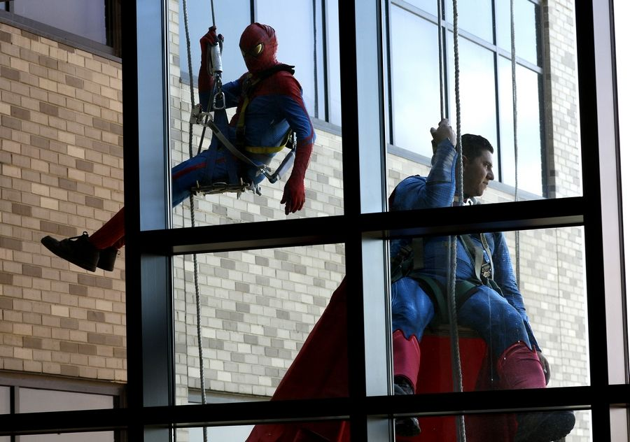 Daniel White/dwhite@dailyherald.comWindow washers dressed as Spider-Man and Superman draw a crowd of onlookers at Northwestern Medicine Central DuPage Hospital. Tom Morrow of West Chicago owns TJ Maintenance, Inc., a company that is contracted to clean the hospital's windows.