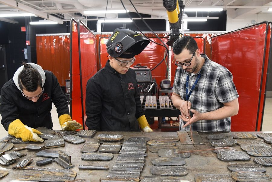 "Elgin High School senior Arturo Gomez gets help from certified welding instructor Nick Moran during a class at the school. Moran says there is a huge demand for entry-level welders in the region, which he calls a ""golden corridor"" of manufacturing industries."