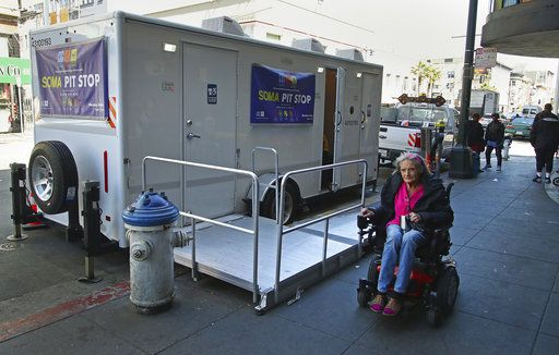 In this photo taken on Thursday, April 26, 2018, a woman in a wheelchair passes a Pit Stop in San Francisco. The Pit Stop program provides public toilets, sinks, used needle receptacles and dog waste stations in San Francisco's most impacted neighborhoods.