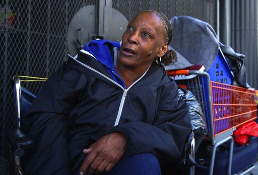 In this photo taken on Thursday, April 26, 2018, Lawana Tillman sits in a wheelchair with her belongings in San Francisco. Tillman camps out in a wheelchair with friends on a corner they've claimed near Market Street. Most of them have been homeless for years. The women say they welcome help, but haven't seen any offers.
