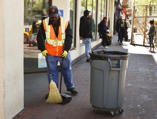 In this photo taken on Thursday, April 26, 2018, a city sanitation worker sweeps Market Street in San Francisco. San Francisco may have hit peak saturation with the stinky urine, used syringes and trash littering its filthy streets and city leaders are paying attention. Mayor Mark Farrell has promised $750,000 to hire more people to pick up discarded needles and $13 million over the next two years for more heavy duty steam cleaners and pit stop toilets.