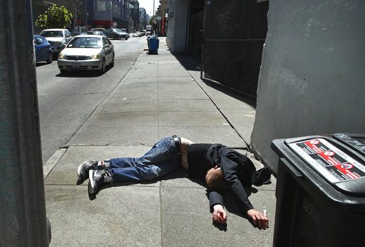 In this photo taken on Thursday, April 26, 2018, a man lies on the sidewalk beside a recyclable trash bin in San Francisco. San Francisco may have hit peak saturation with tent camps, stinky urine and trash littering its filthy streets. And Mark Farrell, a new interim mayor, has vowed to do something about it. The city has long tolerated overflowing trash bins and homeless people who camp out on sidewalks, but Farrell says the squalor isn't safe.