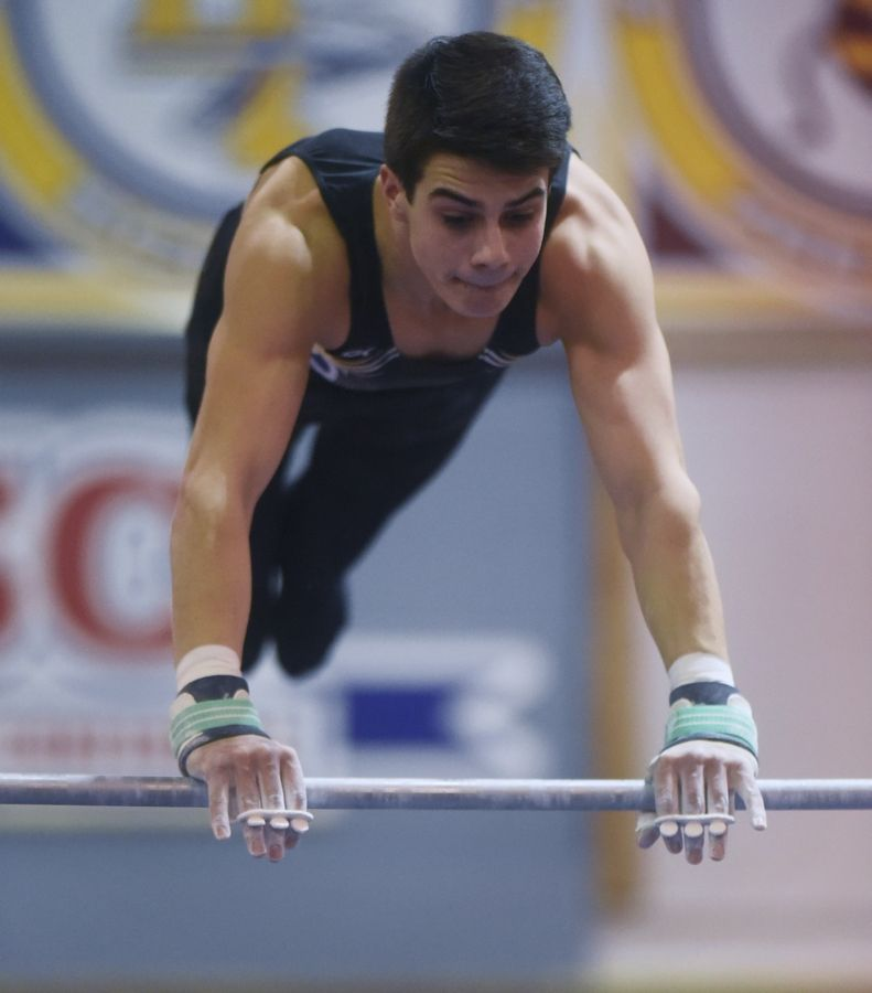 Rolling Meadows' Benjamin Kowalski competes on the high bar during Tuesday's boys gymnastics sectional at Mundelein.