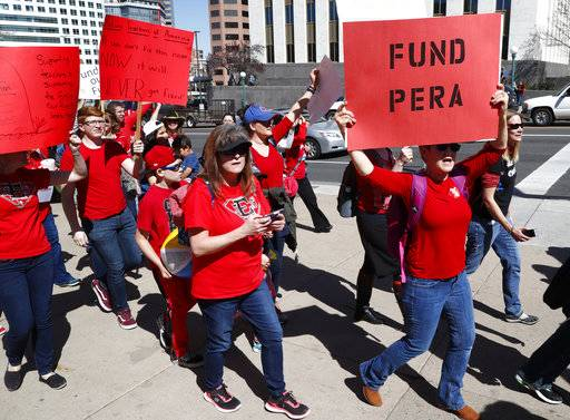 In this April 27, 2018, photograph, a teacher carries a placard in support of funding the teacher and other public sector workers' pension fund during a rally in Denver. Rising pension costs are eating away at teacher pay in Colorado and other states. The pension issue has played a role in a teacher uprising sweeping the U.S. Thousands of Colorado teachers walked off the job and closed down schools last week.
