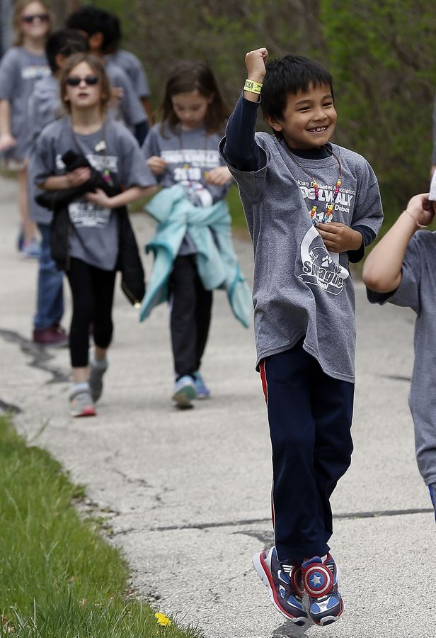 Second-grader student Adrian Gualdron, 7, reacts after getting some cars to honk in support Friday as he and other students and staff walk along the path near Riverwoods Road to reach Ryerson Woods during the School Walk for Diabetes at Sprague School in Lincolnshire. Last year, students collected more than $23,700 for the American Diabetes Association.