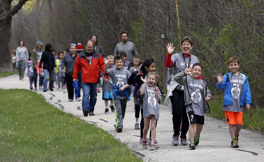 Sprague School teacher Diane Ferron, waving, walks with her second grade class along the path near Riverwoods Road to reach Ryerson Woods Friday during the School Walk for Diabetes in Lincolnshire. Last year, students collected more than $23,700 for the American Diabetes Association.