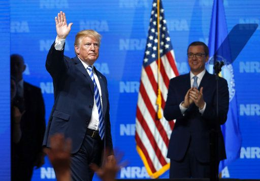 President Donald Trump waves to the audience as Chris Cox, right, executive director of the National Rifle Association-Institute for Legislative Action Leadership Forum after Trump spoke at the annual meeting in Dallas, Friday, May 4, 2018.