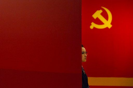 A staff member stands near a Communist Party flag at an exhibition to commemorate the 200th anniversary of the birth of Karl Marx at the National Museum in Beijing, Saturday, May 5, 2018. Abroad, China's President Xi Jinping portrays himself as a robust defender of free markets, yet at home, he's leading a campaign to promote the works of communist philosopher Karl Marx, who famously warned of the dangers of global capitalism.