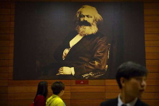 Visitors walk past a photograph of Karl Marx at an exhibition to commemorate the 200th anniversary of his birth at the National Museum in Beijing, Saturday, May 5, 2018. Abroad, China's President Xi Jinping portrays himself as a robust defender of free markets, yet at home, he's leading a campaign to promote the works of communist philosopher Karl Marx, who famously warned of the dangers of global capitalism.