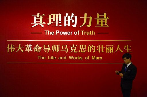 A staff member stands at the entrance to an exhibition to commemorate the 200th anniversary of the birth of Karl Marx at the National Museum in Beijing, Saturday, May 5, 2018. Abroad, China's President Xi Jinping portrays himself as a robust defender of free markets, yet at home, he's leading a campaign to promote the works of communist philosopher Karl Marx, who famously warned of the dangers of global capitalism.