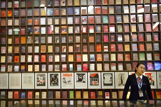 A staff member stands in front of a display of editions of the Communist Manifesto in different languages at an exhibition to commemorate the 200th anniversary of the birth of Karl Marx at the National Museum in Beijing, Saturday, May 5, 2018. Abroad, China's President Xi Jinping portrays himself as a robust defender of free markets, yet at home, he's leading a campaign to promote the works of communist philosopher Karl Marx, who famously warned of the dangers of global capitalism.