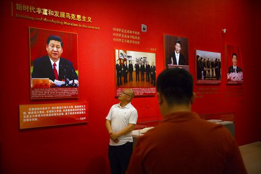 "A visitor looks at a display with photos of Chinese President Xi Jinping titled ""Enriching and developing Marxism in the new era"" at an exhibition to commemorate the 200th anniversary of the birth of Karl Marx at the National Museum in Beijing, Saturday, May 5, 2018. Abroad, China's President Xi Jinping portrays himself as a robust defender of free markets, yet at home, he's leading a campaign to promote the works of communist philosopher Karl Marx, who famously warned of the dangers of global capitalism."