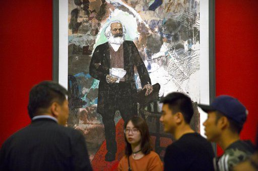Visitors look at paintings at an exhibition to commemorate the 200th anniversary of the birth of Karl Marx at the National Museum in Beijing, Saturday, May 5, 2018. Abroad, China's President Xi Jinping portrays himself as a robust defender of free markets, yet at home, he's leading a campaign to promote the works of communist philosopher Karl Marx, who famously warned of the dangers of global capitalism.