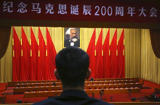 "In this Friday, May 4, 2018, photo, a security person waits before the start of an event to mark the bicentennial of Karl Marx's birth near a banner which reads: ""Commemorate Karl Marx birth 200th anniversary"" at the Great Hall of the People in Beijing. Abroad, China's President Xi Jinping portrays himself as a robust defender of free markets, yet at home, he's leading a campaign to promote the works of communist philosopher Karl Marx, who famously warned of the dangers of global capitalism."