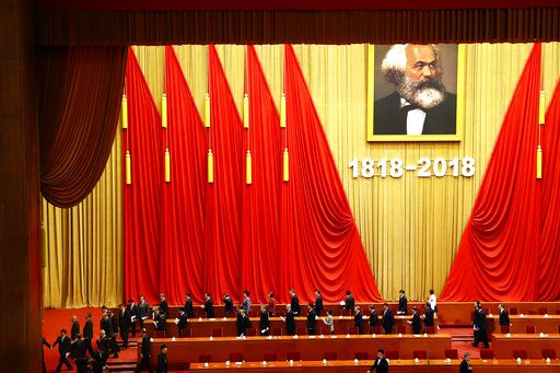 In this May 4, 2018, photo, participants leave after an event to mark the bicentennial of Karl Marx's birth at the Great Hall of the People in Beijing. Abroad, China's President Xi Jinping portrays himself as a robust defender of free markets, yet at home, he's leading a campaign to promote the works of communist philosopher Karl Marx, who famously warned of the dangers of global capitalism.