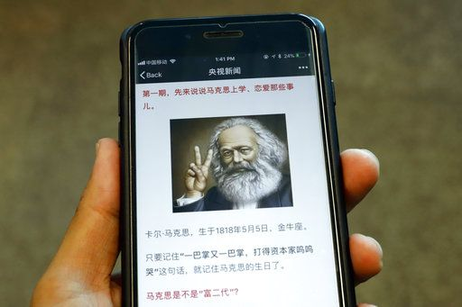 "This May 4, 2018, photo shows an illustration of Karl Marx making a trendy v-for-victory sign with two fingers that's part of a media campaign with a catch theme song, dramatic readings that declared ""Marx was Correct"" on a smartphone, in Beijing. Abroad, China's President Xi Jinping portrays himself as a robust defender of free markets, yet at home, he's leading a campaign to promote the works of communist philosopher Karl Marx, who famously warned of the dangers of global capitalism."