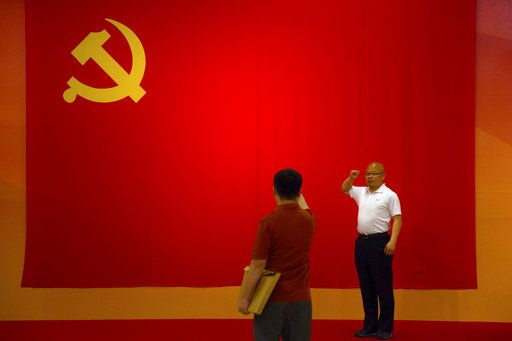 A visitor gestures as he poses for a photo in front of a Communist Party flag at an exhibition to commemorate the 200th anniversary of the birth of Karl Marx at the National Museum in Beijing, Saturday, May 5, 2018. Abroad, China's President Xi Jinping portrays himself as a robust defender of free markets, yet at home, he's leading a campaign to promote the works of communist philosopher Karl Marx, who famously warned of the dangers of global capitalism.