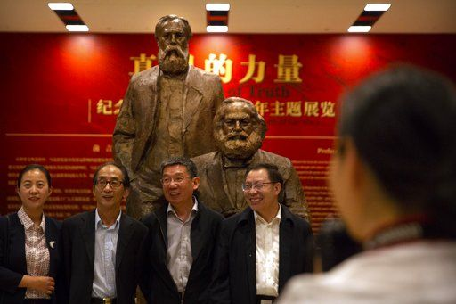 Visitors line up for a group photo in front of a sculpture of Karl Marx and Friedrich Engels at an exhibition to commemorate the 200th anniversary of the birth of Marx at the National Museum in Beijing, Saturday, May 5, 2018. Abroad, China's President Xi Jinping portrays himself as a robust defender of free markets, yet at home, he's leading a campaign to promote the works of communist philosopher Karl Marx, who famously warned of the dangers of global capitalism.
