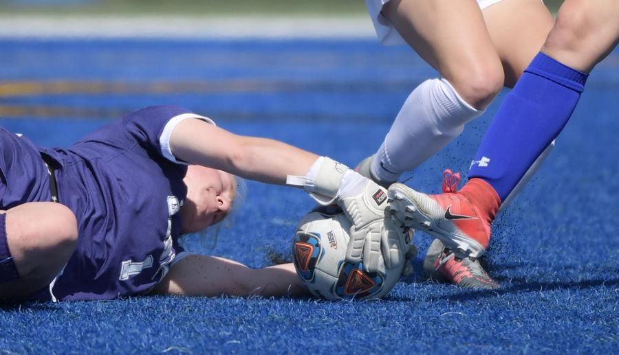 Geneva goalkeeper Katie Montgomery dives to wrap up a loose ball as Burlington Central's Zoey Kollhoff challenges in a girls soccer game Saturday in Geneva. Geneva's Kaitlyn Cannon also defends.