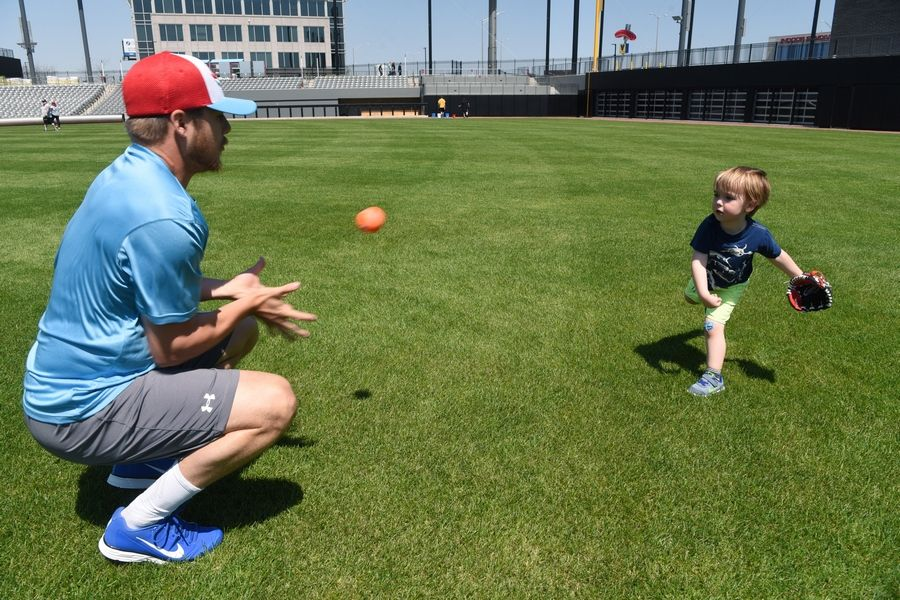 Chicago Dogs left-handed pitcher Tommy Thorpe plays catch with Jack O'Connor, 3, of Park Ridge during an open house at Impact Field in Rosemont Saturday.