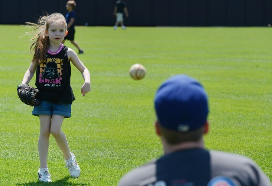 Katie Lee, 6, of Elmwood Park plays catch with her dad, Greg, during an open house at Impact Field in Rosemont Saturday.