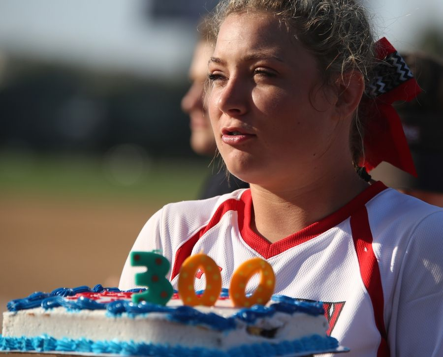 Huntley's Sofia Tenuta unveils a cake in honor of head coach Mark Petryniec's 300th career victory during varsity softball at Hampshire Monday. Huntley blanked the host Whip-Purs 13-0 in five innings.