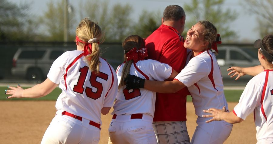 Coach Mark Petryniec is mobbed by Huntley players after a win during varsity softball at Hampshire Monday. Huntley blanked the host Whip-Purs 13-0 in five innings as Petryniec notched his 300th career victory.