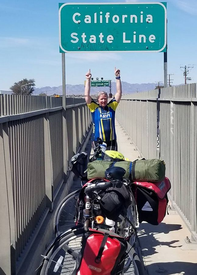 Tracy Sefcik of Wheeling at the California state line during her cross-country bike journey.