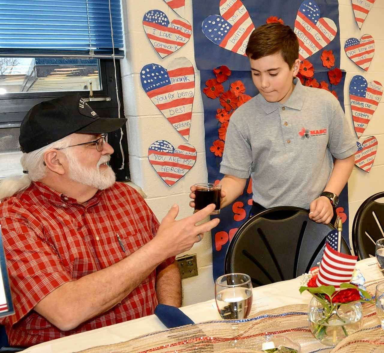 Fremont Middle School sixth-grader Ramsen Marano serves a drink to veteran Saford Wilson during the recent veterans dinner sponsored by the Mundelein Police Department.