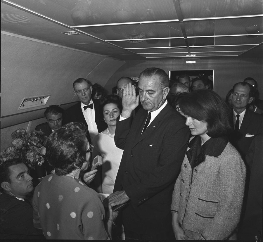 Lyndon B. Johnson takes the oath of office aboard Air Force One in Dallas on Nov. 22, 1963, with Jacqueline Kennedy watching.