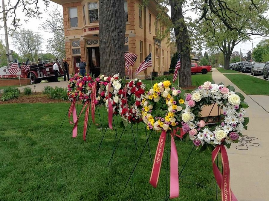 Floral wreaths donated by the participating fire departments await the start of the 26th annual Elgin Area Firefighters' Memorial Service Saturday in front of the Elgin Fire Barn No. 5 Museum.